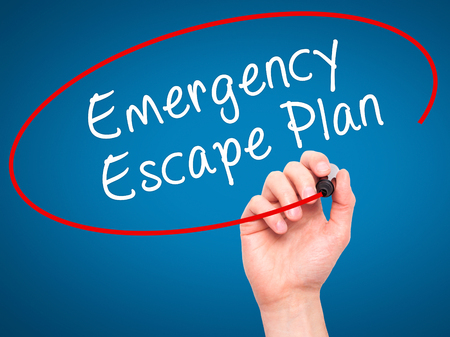 Foto de Man Hand writing Emergency Escape Plan with black marker on visual screen. Isolated on blue. Business, technology, internet concept. Stock Image - Imagen libre de derechos
