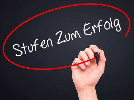 Man Hand writing Stufen Zum Erfolg (Steps to Success in German) with black marker on visual screen. Isolated on black. Business, technology, internet concept. Stock Photo
