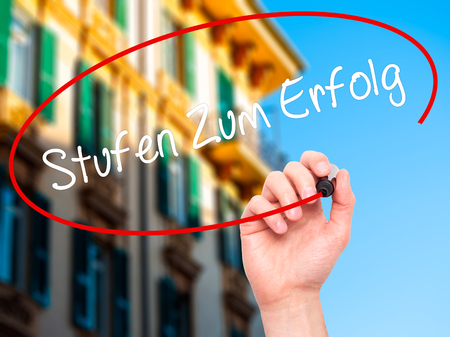 Man Hand writing Stufen Zum Erfolg (Steps to Success in German) with black marker on visual screen. Isolated on city. Business, technology, internet concept. Stock Photo