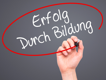 Man Hand writing Erfolg Durch Bildung  (Success Through Training in German) with black marker on visual screen. Isolated on background. Business, technology, internet concept. Stock Photo