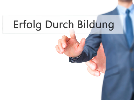 Erfolg Durch Bildung (Success Through Training in German) - Businessman hand pressing button on touch screen interface. Business, technology, internet concept. Stock Photo