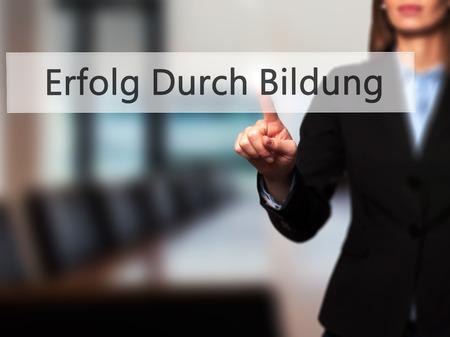 Erfolg Durch Bildung (Success Through Training in German) - Businesswoman hand pressing button on touch screen interface. Business, technology, internet concept. Stock Photo