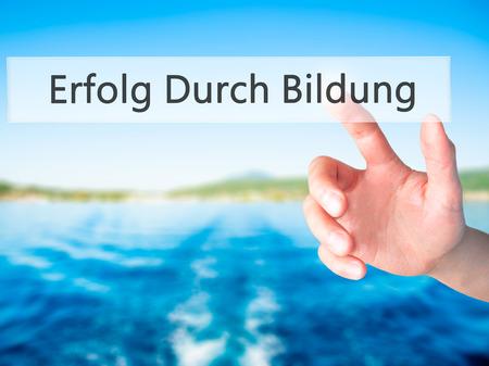 Erfolg Durch Bildung (Success Through Training in German) - Hand pressing a button on blurred background