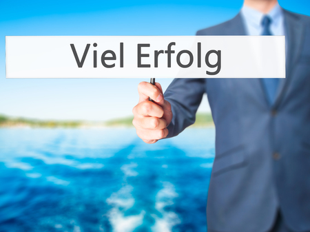 Viel Erfolg  (Much Success In German) - Businessman hand holding sign. Business, technology, internet concept. Stock Photo