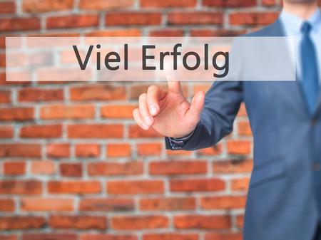 Viel Erfolg  (Much Success In German) - Businessman hand pressing button on touch screen interface.