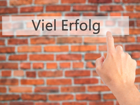Viel Erfolg  (Much Success In German) - Hand pressing a button on blurred background concept . Business, technology, internet concept. Stock Photo