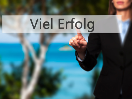 Viel Erfolg  (Much Success In German) - Businesswoman hand pressing button on touch screen interface.