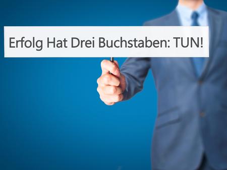 Erfolg Hat Drei Buchstaben: Tun! (Success Has Three Letters: Do in German) - Businessman hand holding sign. Business, technology, internet concept. Stock Photo