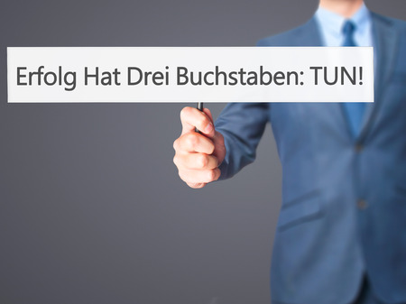 Erfolg Hat Drei Buchstaben: Tun! (Success Has Three Letters: Do in German) - Businessman hand holding sign. Business, technology, internet concept. Stock Photo