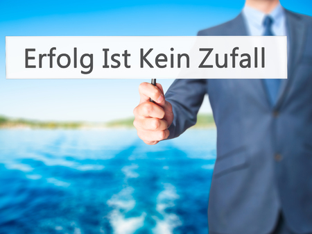 Erfolg Ist Kein Zaufall (Success Is No Accident in German) - Businessman hand holding sign. Business, technology, internet concept. Stock Photo