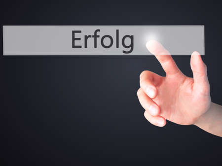 Erfolg (Success) - Hand pressing a button on blurred background concept . Business, technology, internet concept. Stock Photo