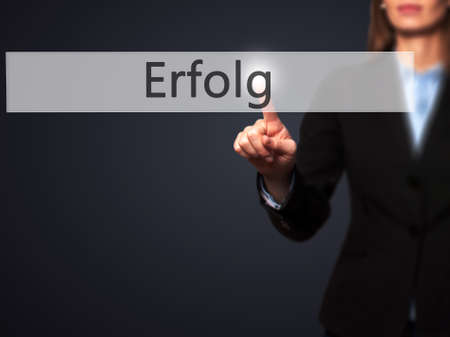 Erfolg (Success) - Businesswoman hand pressing button on touch screen interface. Business, technology, internet concept. Stock Photo