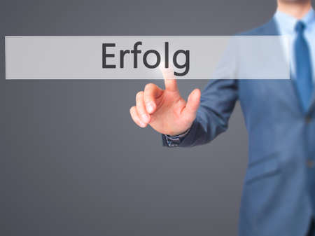 Erfolg (Success)  - Businessman hand pressing button on touch screen interface. Business, technology, internet concept. Stock Photo