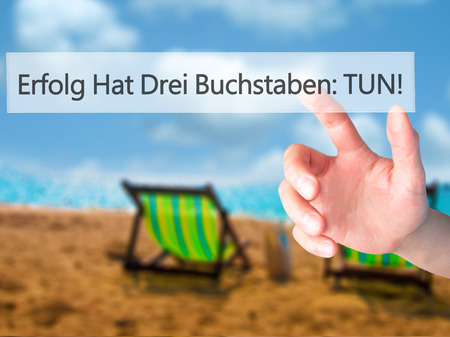 Erfolg Hat Drei Buchstaben: Tun! (Success Has Three Letters: Do in German) - Hand pressing a button on blurred background concept . Business, technology, internet concept. Stock Photo