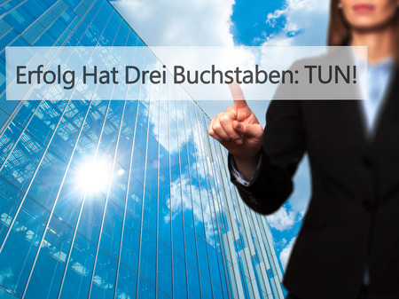Erfolg Hat Drei Buchstaben: Tun! (Success Has Three Letters: Do in German) - Businesswoman hand pressing button on touch screen interface. Business, technology, internet concept. Stock Photo
