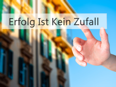 Erfolg Ist Kein Zaufall (Success Is No Accident in German) - Hand pressing a button on blurred background concept . Business, technology, internet concept. Stock Photo