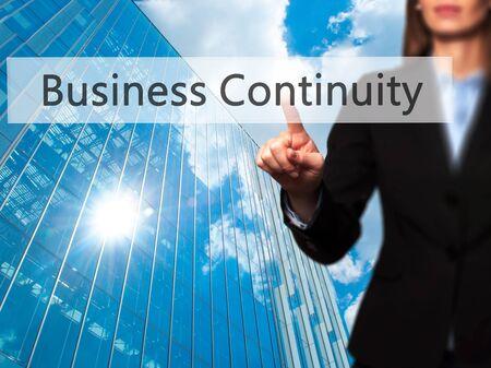 Foto de Business Continuity - Businesswoman pressing high tech  modern button on a virtual background. Business, technology, internet concept. Stock Photo - Imagen libre de derechos