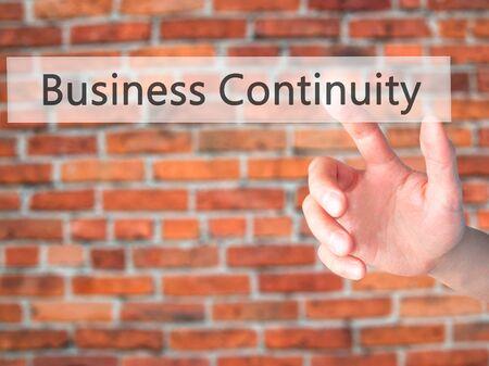 Foto de Business Continuity - Hand pressing a button on blurred background concept . Business, technology, internet concept. Stock Photo - Imagen libre de derechos