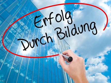 Man Hand writing Erfolg Durch Bildung  (Success Through Training in German) with black marker on visual screen.  Business, technology, internet concept. Modern business skyscrapers background. Stock Photo