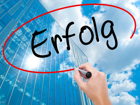 Man Hand writing Erfolg Success (in German) with black marker on visual screen. Business, technology, internet concept. Modern business skyscrapers background. Stock Photo
