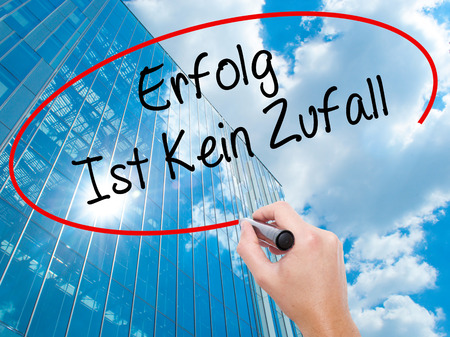 Man Hand writing Erfolg Ist Kein Zaufall (Success Is No Accident in German) with black marker on visual screen.  Business, technology, internet concept. Modern business skyscrapers background. Stock Photo