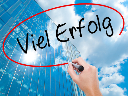 Man Hand writing Viel Erfolg (Much Success In German) with black marker on visual screen.  Business, technology, internet concept. Modern business skyscrapers background. Stock Photo