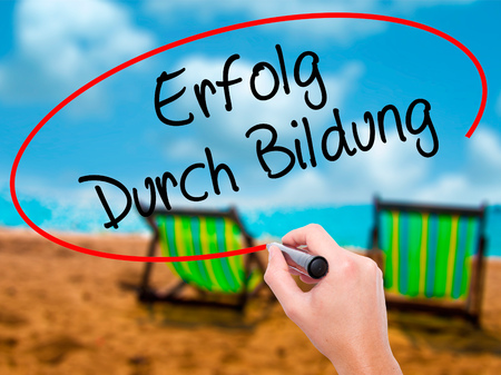 Man Hand writing Erfolg Durch Bildung  (Success Through Training in German) with black marker on visual screen. Isolated on sunbed on the beach. Business, technology, internet concept. Stock Photo