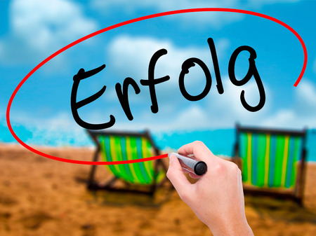 Man Hand writing Erfolg Success (in German) with black marker on visual screen. Isolated on sunbed on the beach. Business, technology, internet concept. Stock Photo