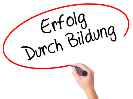 Women Hand writing Erfolg Durch Bildung  (Success Through Training in German) with black marker on visual screen. Isolated on white. Business, technology, internet concept. Stock Photo