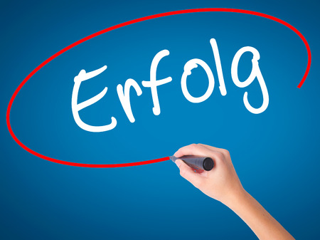 Women Hand writing Erfolg Success (in German) with black marker on visual screen. Isolated on blue. Business, technology, internet concept. Stock Photo