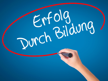 Women Hand writing Erfolg Durch Bildung  (Success Through Training in German) with black marker on visual screen. Isolated on blue. Business, technology, internet concept. Stock Photo