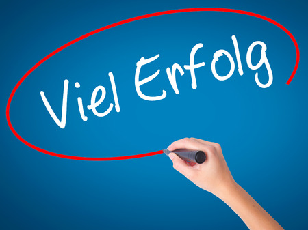 Women Hand writing Viel Erfolg (Much Success In German) with black marker on visual screen. Isolated on blue. Business, technology, internet concept. Stock Photo
