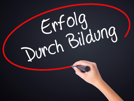 Woman Hand Writing Erfolg Durch Bildung  (Success Through Training in German) on blank transparent board with a marker isolated over black background. Stock Photo