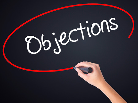 Photo pour Woman Hand Writing Objections  on blank transparent board with a marker isolated over black background. Business concept. Stock Photo - image libre de droit