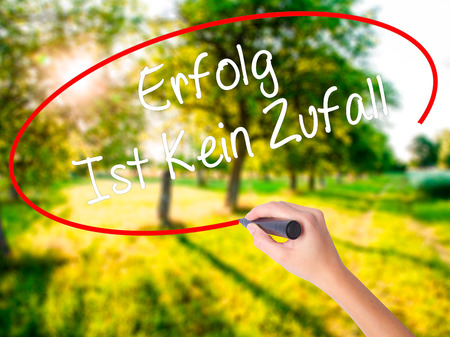 Woman Hand Writing Erfolg Ist Kein Zaufall (Success Is No Accident in German) on blank transparent board with a marker isolated over green field background. Stock Photo