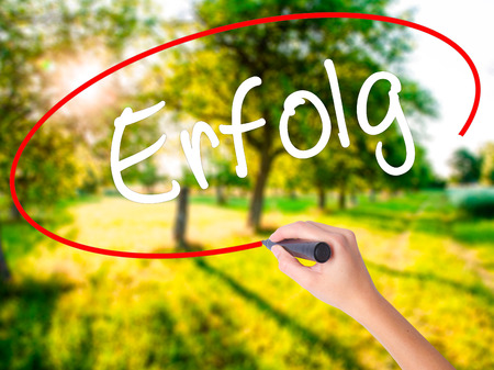 Woman Hand Writing Erfolg Success (in German) on blank transparent board with a marker isolated over green field background. Business concept. Stock Photo