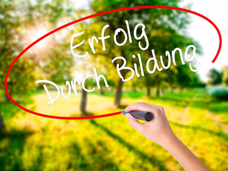Woman Hand Writing Erfolg Durch Bildung  (Success Through Training in German) on blank transparent board with a marker isolated over green field background. Stock Photo