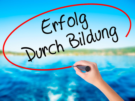 Woman Hand Writing Erfolg Durch Bildung  (Success Through Training in German) on blank transparent board with a marker isolated over water background. Business concept. Stock Photo
