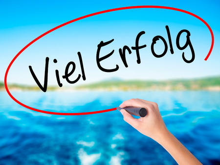 Woman Hand Writing Viel Erfolg (Much Success In German) on blank transparent board with a marker isolated over water background. Business concept. Stock Photo
