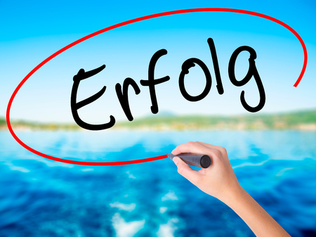 Woman Hand Writing Erfolg Success (in German) on blank transparent board with a marker isolated over water background. Business concept. Stock Photo
