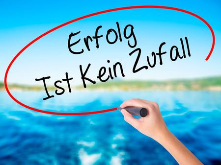Woman Hand Writing Erfolg Ist Kein Zaufall (Success Is No Accident in German) on blank transparent board with a marker isolated over water background. Business concept. Stock Photo