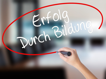 Woman Hand Writing Erfolg Durch Bildung  (Success Through Training in German) with a marker over transparent board. Isolated on Office. Business concept. Stock Photo
