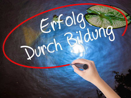 Woman Hand Writing Erfolg Durch Bildung  (Success Through Training in German) with marker over transparent board. Isolated on nature. Business concept. Stock Photo