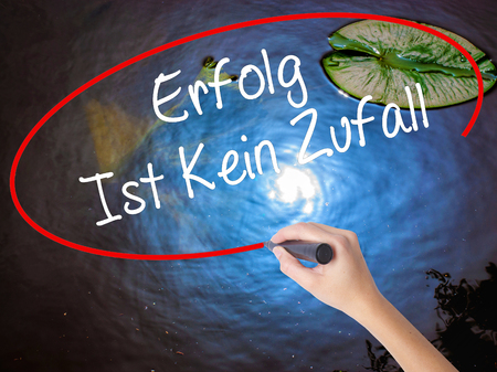 Woman Hand Writing Erfolg Ist Kein Zaufall (Success Is No Accident in German) with marker over transparent board. Isolated on nature. Business concept. Stock Photo