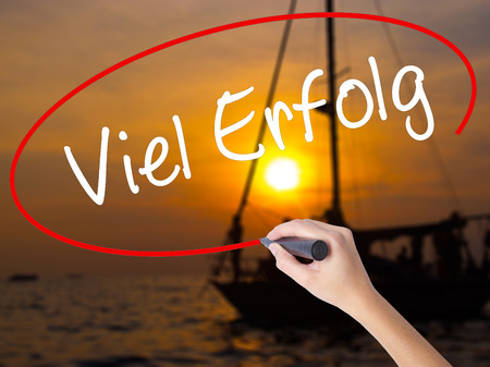 Woman Hand Writing Viel Erfolg (Much Success In German) with a marker over transparent board. Isolated on Sunset Boat. Business concept. Stock Photo