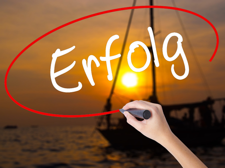 Woman Hand Writing Erfolg Success (in German) with a marker over transparent board. Isolated on Sunset Boat. Business concept. Stock Photo