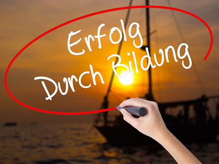 Woman Hand Writing Erfolg Durch Bildung  (Success Through Training in German) with a marker over transparent board. Isolated on Sunset Boat. Business concept. Stock Photo