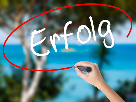Woman Hand Writing Erfolg Success (in German) with black marker on visual screen. Isolated on nature. Business concept. Stock Photo