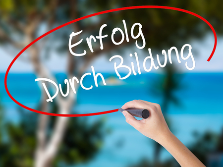 Woman Hand Writing Erfolg Durch Bildung  (Success Through Training in German) with black marker on visual screen. Isolated on nature. Business concept. Stock Photo