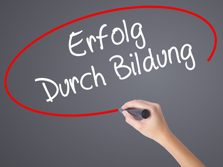 Woman Hand Writing Erfolg Durch Bildung  (Success Through Training in German) with black marker on visual screen. Isolated on grey. Business concept. Stock Photo